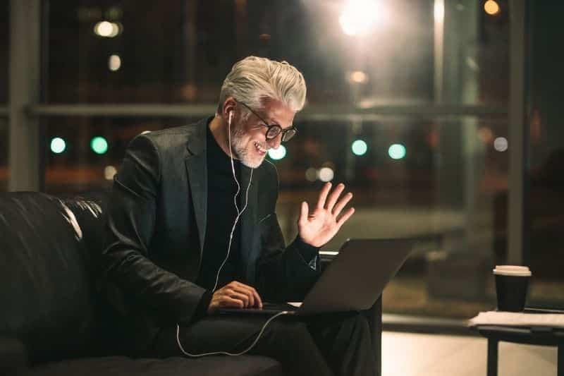 Hombre canoso con gafas y auriculares saluda en una videollamada por la noche
