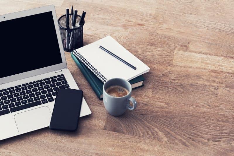 Escritorio con pc, móvil, café, libreta y bolígrafos