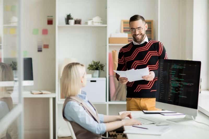 ingeniera de software en oficina con chico hablándole con papeles